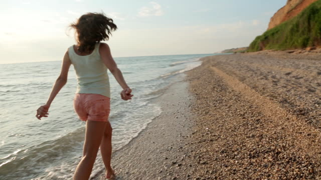 Cheerful girl with a beautiful smile, wearing in shorts and a T-shirt runs barefoot through the water along a deserted beach video
