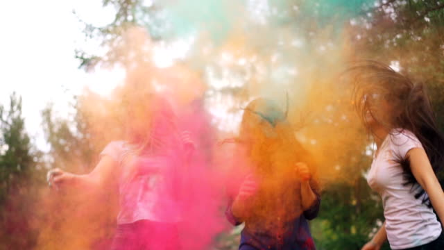 cheerful girls are having fun dancing and laughing in clouds of powder paint at holi festival wearing trendy clothing stained with paint. youth and happiness concept. - generazione y video stock e b–roll