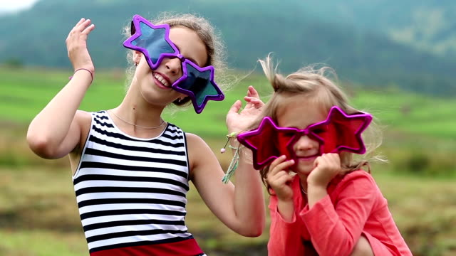 Cheerful girls in big glasses in the shape of stars looks at the camera video