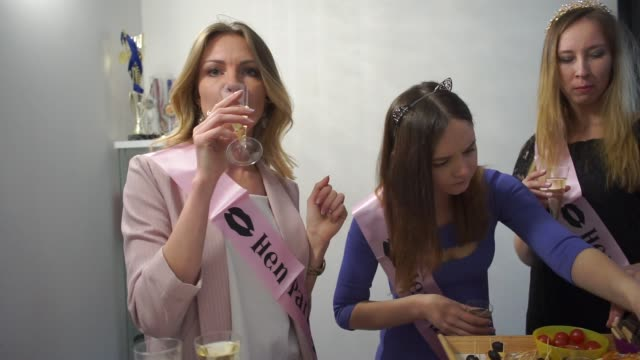 Cheerful girls take food at a buffet table. They drink champagne.