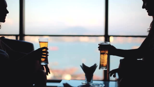 Cheerful girls talking, cheering drinking beer sitting by the window with urban view. 1920x1080 Cheerful girls talking, cheering drinking beer sitting by the window with urban view. 1920x1080, hd sleeve stock videos & royalty-free footage
