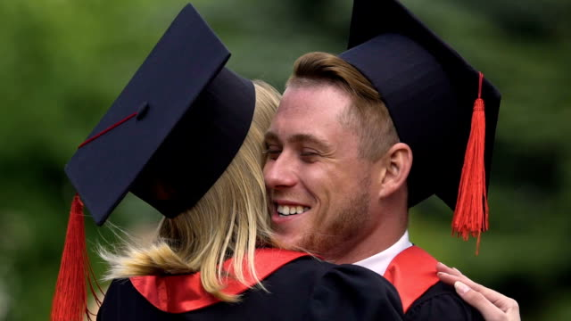 Cheerful graduate embracing girlfriend, people enjoying success and laughing video