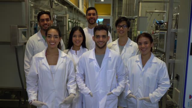 Cheerful group of chemistry students at a laboratory facing camera smiling very happy