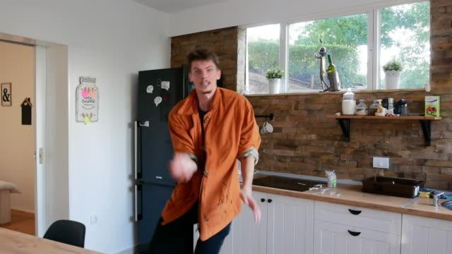 glad kille som dansar i köket - lång längd bildbanksvideor och videomaterial från bakom kulisserna