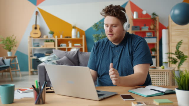 Cheerful guy in headphones listening to music dancing working with laptop at home video