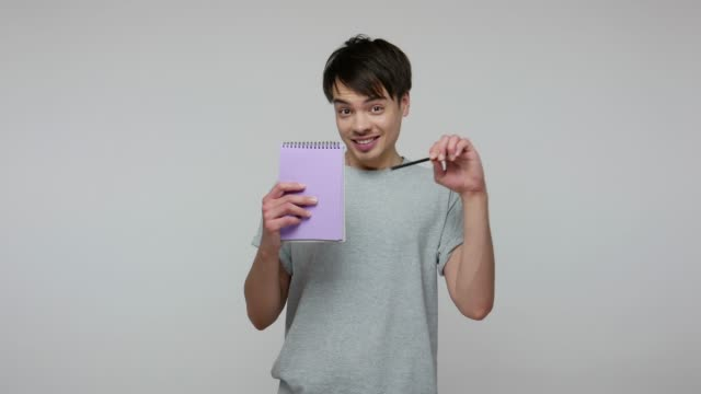 Cheerful guy in T-shirt pointing paper notebook and looking at camera with toothy smile, offering to write idea