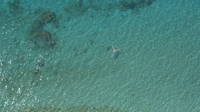 AERIAL: Cheerful guy swimming starfish float and relaxing in crystal clear ocean video