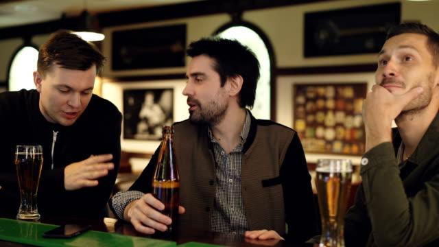 Chicos guapos alegres tiene conversación en la barra sobre la cerveza. Hombres jóvenes están sosteniendo botellas y vasos, charlando y gesticulando emocionalmente. - vídeo