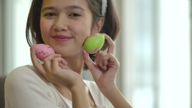 Cheerful happy girl, paint on fantasy easter eggs with a brush beautiful decorative of handmade, show colourful of the eggs at camera. Holidays and people the symbolic of Easter egg festival concept.