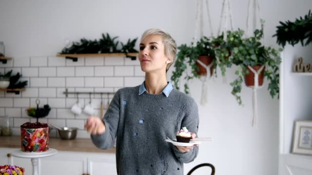 cheerful happy woman standing on the kitchen, throw small marshmallow and catch it with her mouth. short grey haired woman in modern bright kitchen standing with cupcake on late in her hand. having fun while cooking - ловить стоковые видео и кадры b-roll