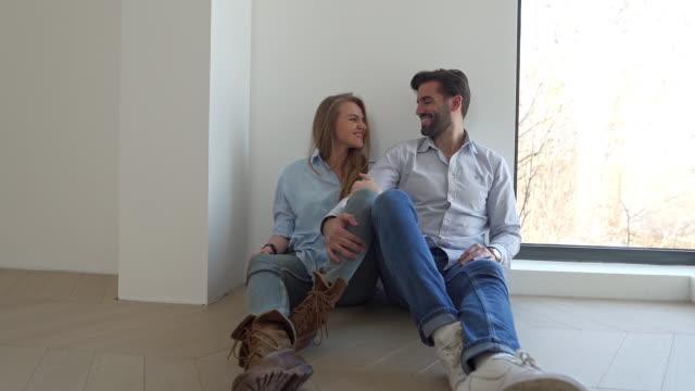 陽気な幸せな若い夫婦は、彼らの新しい家で初日を楽しんでいます ビデオ