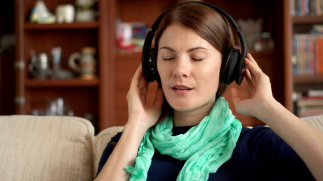 Cheerful happy young woman at home listening music with wireless cordless headphones and singing Cheerful happy young woman at home listening music with wireless cordless headphones and singing. Relaxing, having fun, feeling freedom cordless phone stock videos & royalty-free footage
