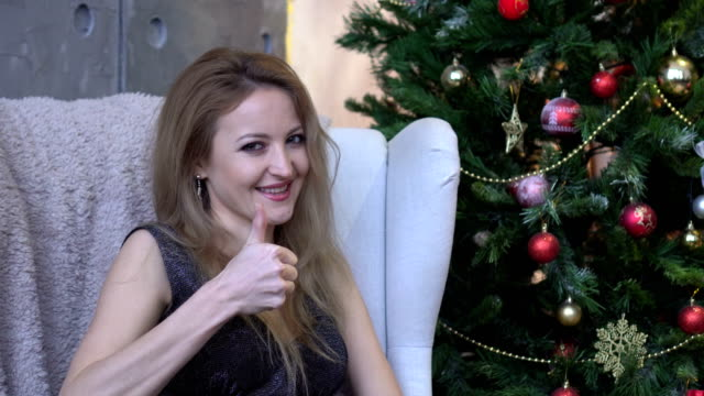 Cheerful happy young woman showing thumb up on christmas tree background video