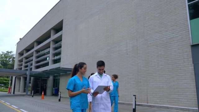 tablete bakan bir vakadan bahsederken hastaneden çıkan neşeli sağlık çalışanları - cerrahi önlük stok videoları ve detay görüntü çekimi