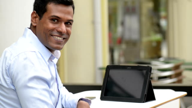 Cheerful Indian Businessman using Digital Tablet at Outdoor Cafe video