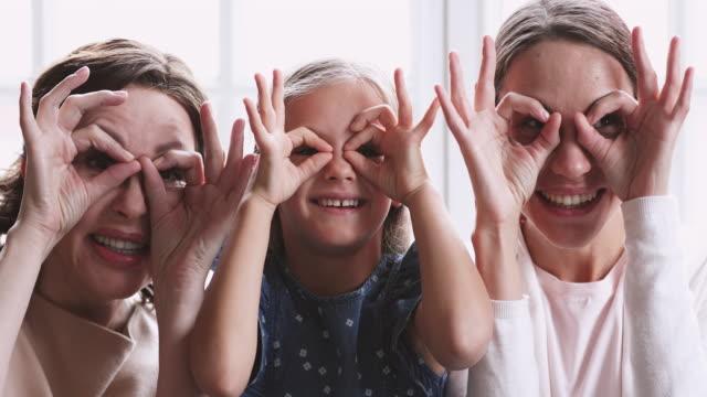fröhliche generationenübergreifende familie machen lustige gläser lachen blick in die kamera - menschlicher kopf stock-videos und b-roll-filmmaterial