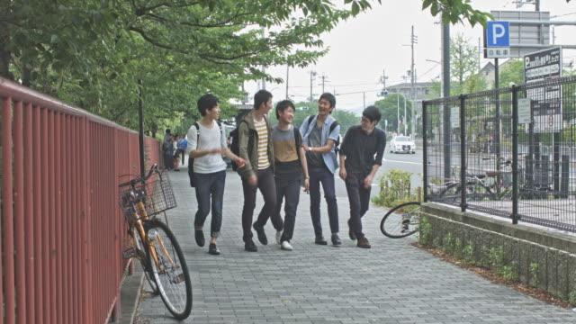 京都で歩道の上を歩く陽気な日本の大学生 - アジア旅行点の映像素材/bロール