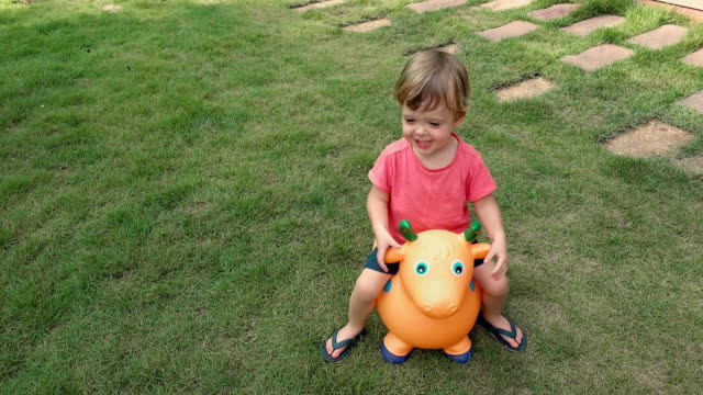 Cheerful kid on rubber toy outdoors Little boy to ride on rubber toy cow on green meadow in yard charming stock videos & royalty-free footage