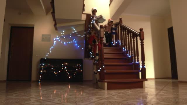 stockvideo's en b-roll-footage met vrolijke kinderen uitvoering presenteert naar beneden. - christmas tree
