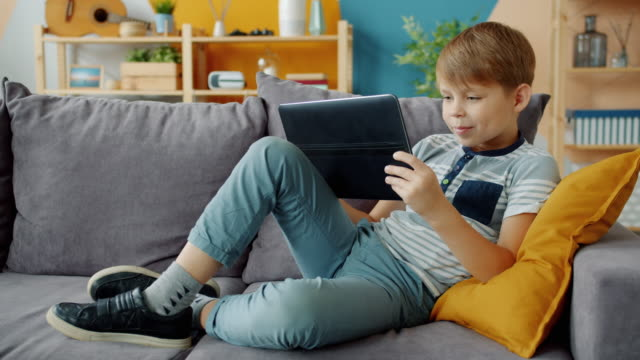 Cheerful little boy holding tablet using modern device on couch at home alone Cheerful little boy is holding tablet using modern device on couch at home alone enjoying video content. Childhood, gadgets and modern people concept. one boy only stock videos & royalty-free footage