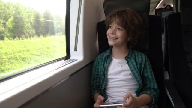 スマホでゲームをして、電車の中で通勤しながら見ている陽気な少年 - 男の子点の映像素材/bロール