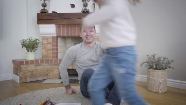 Cheerful little Caucasian girl running around adult man holding his hand, smiling father taking his lovely daughter on hands. Portrait of happy parent and child having fun indoors. Camera zooming in.