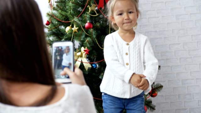 Cheerful little girl dancing and playing the ape near Christmas tree video