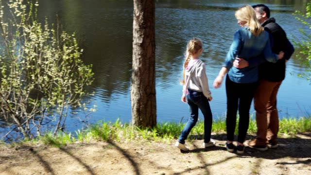 vídeos de stock e filmes b-roll de cheerful little girl hopping in forest towards her parents standing near lake. lovely family of three embracing and admiring view, tracking right shot - man admires forest
