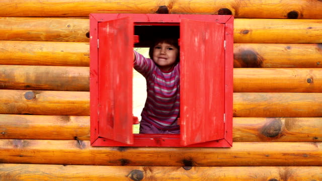Cheerful little girl in the wooden hut