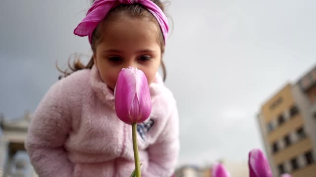 Cheerful little girl smelling tulips and playing around city centre
