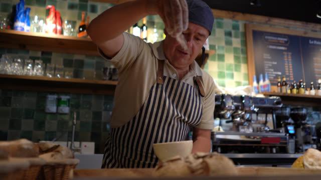 vidéos et rushes de le boulanger mâle gai saupoudrant la farine sur le pain très heureux - boulanger