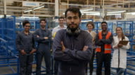 istock Cheerful male blue collar worker wearing protective ear muffs on neck smiling at camera and group of employees standing behind 1206324549