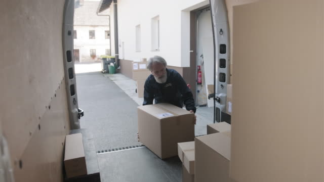 cheerful male gig delivery driver carrying parcel off van - rozładowywać filmów i materiałów b-roll