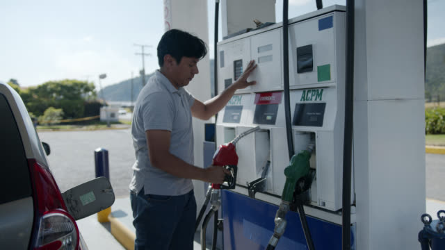 Cheerful man at a self service gas pump service Cheerful man at a self service gas pump service - Business concepts refueling stock videos & royalty-free footage