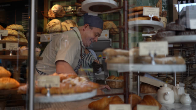 Cheerful man cleaning the counter at a bakery while woman is putting on protective gloves to arrange the bread display video