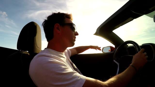 vidéos et rushes de close up: homme gai conduite en cabriolet de luxe, la musique et la danse - homme faire coucou voiture