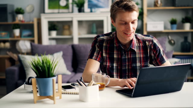 Cheerful man is working at home using laptop sitting at desk typing and smiling