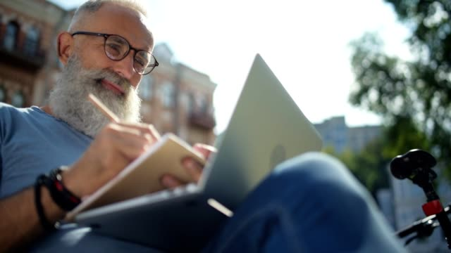 Cheerful man looking at laptop while making notes video