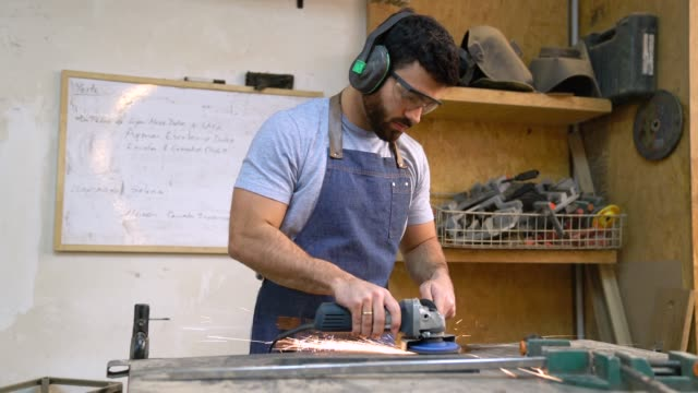 Cheerful man polishing a metal part and then facing camera smiling Cheerful man polishing a metal part and then facing camera smiling at the workshop metalwork stock videos & royalty-free footage