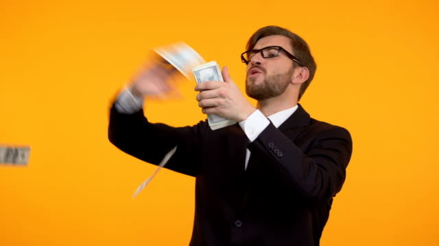Cheerful man throwing money from bunch in his hands, victory, big win, fortune