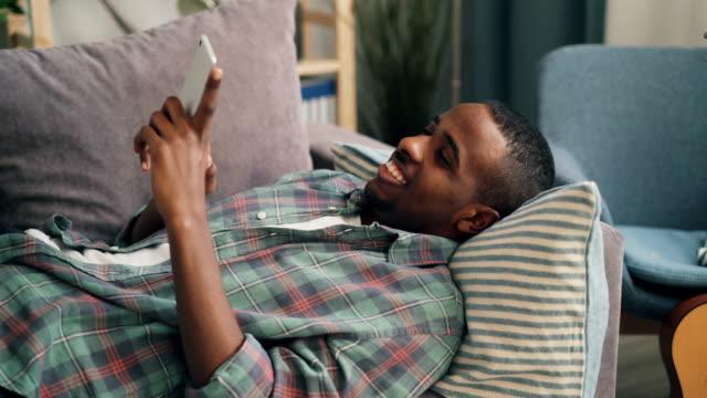 gladlynt man använder smartphone liggande på soffan hemma - endast en man bildbanksvideor och videomaterial från bakom kulisserna