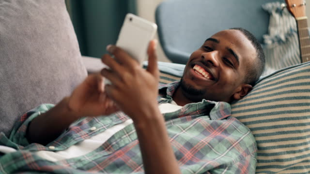 cheerful man using smartphone lying on couch at home - solo un uomo video stock e b–roll