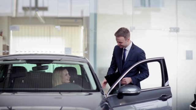 Cheerful manager helping girl with choosing car