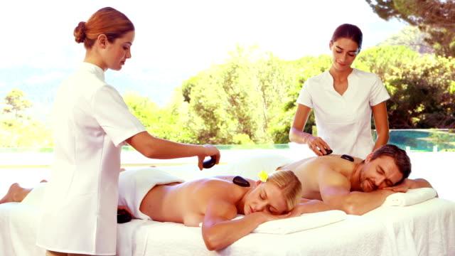 radosne masażyści robi masaż do relaksujące para - terapia lastone filmów i materiałów b-roll