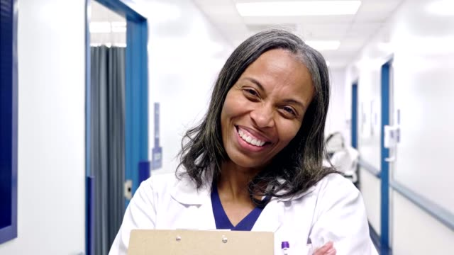 cheerful mature african american female doctor - лабораторный халат стоковые видео и кадры b-roll