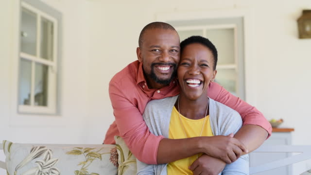 Cheerful mature balck couple Happy mature black couple bonding to each other and smiling while sitting on couch. Portrait of smiling black man embrace his wife from behind and looking at camera. Smiling husband and beautiful woman laughing. falling in love stock videos & royalty-free footage