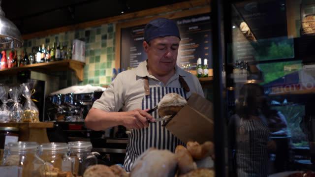 vidéos et rushes de homme mûr gai travaillant à un pain d'emballage de boulangerie dans un sac en papier pour le client féminin très amical et souriant - pâtisseries et feuilletés