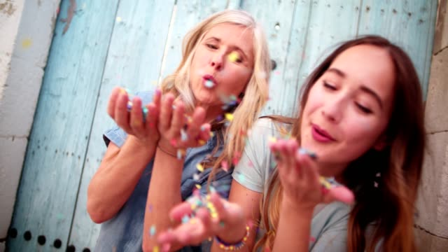 Cheerful mature mother and teenage daughter ceblowing confetti outdoors video