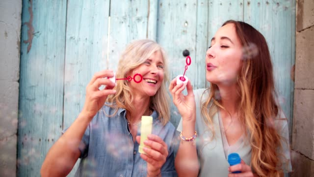Cheerful mature mother and young daughter blowing bubbles outdoors Happy mature mother and teenage daughter blowing bubbles and laughing in old city streets granddaughter stock videos & royalty-free footage