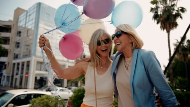 vídeos de stock e filmes b-roll de cheerful mature women celebrating with balloons in the city - mulheres maduras
